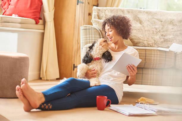 Femme assise sur le sol qui lit des documents avec son chien dans les bras