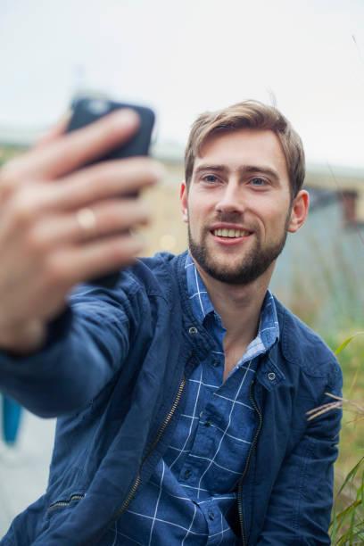 Homme qui se prend en selfie à l'extérieur