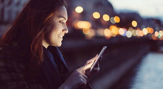 Femme qui envoie un message sur son smartphone à la tombée de la nuit