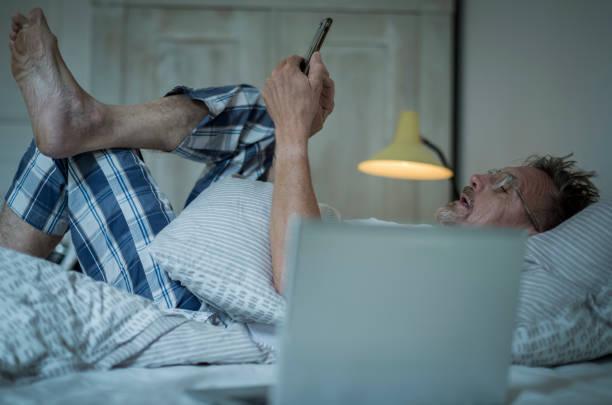 Homme de cinquante ans, en pyjama dans son lit, avec un téléphone portable et un ordinateur