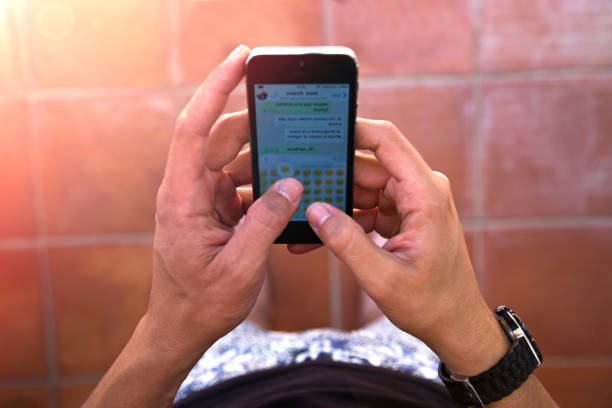 Gros plan sur les mains d'un homme en train d'écrire un SMS