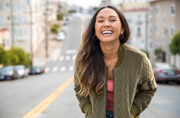 Jeune femme qui sourie en se penchant en avant dans une rue