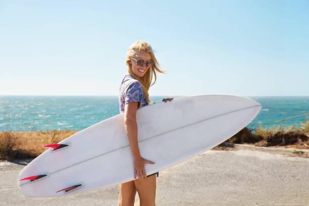 Jeune fille qui tient une planche de surf sur une plage australienne