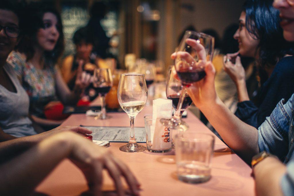 Convives qui boivent du vin rouge pendant un repas de fête