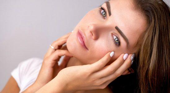 Belle femme brune aux yeux bleus qui tient sa tête penchée entre ses mains