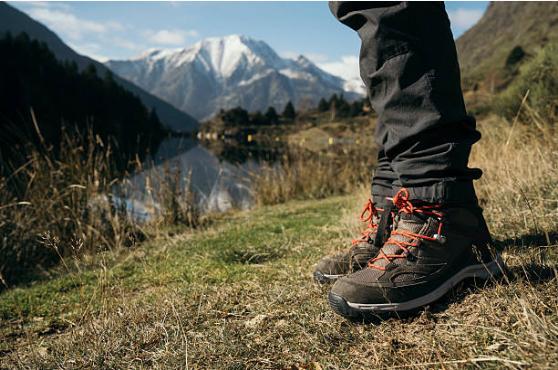 vue sur les pied d'une personne à la montagne portant des chaussures de randonnée