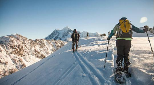 personnes qui font une randonnée en raquettes dans la neige